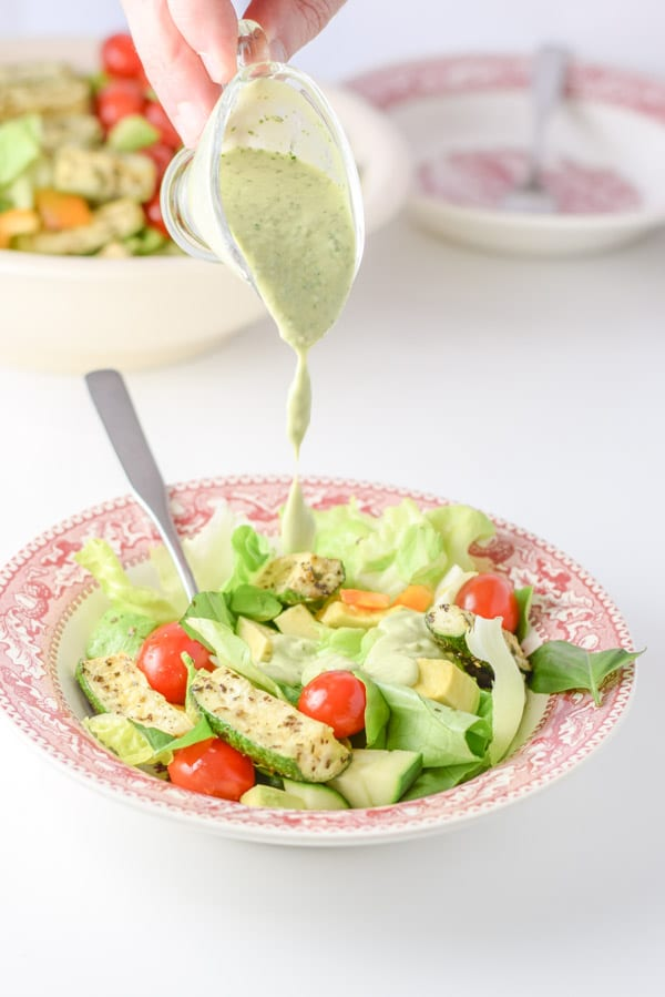 Drips of green dressing going on the salad