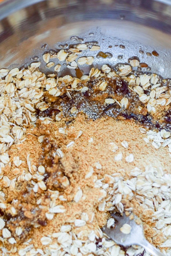 All the ingredients, including oats, chia seeds and flax meal in a metal bowl ready to be mixed