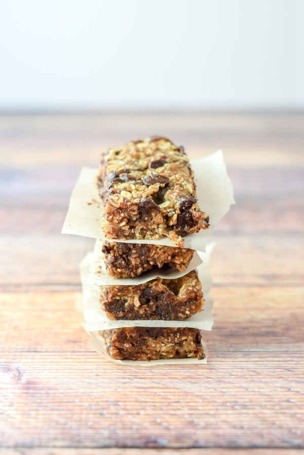 Four chocolate chip granola bars stacked on top of each other with parchment paper between them
