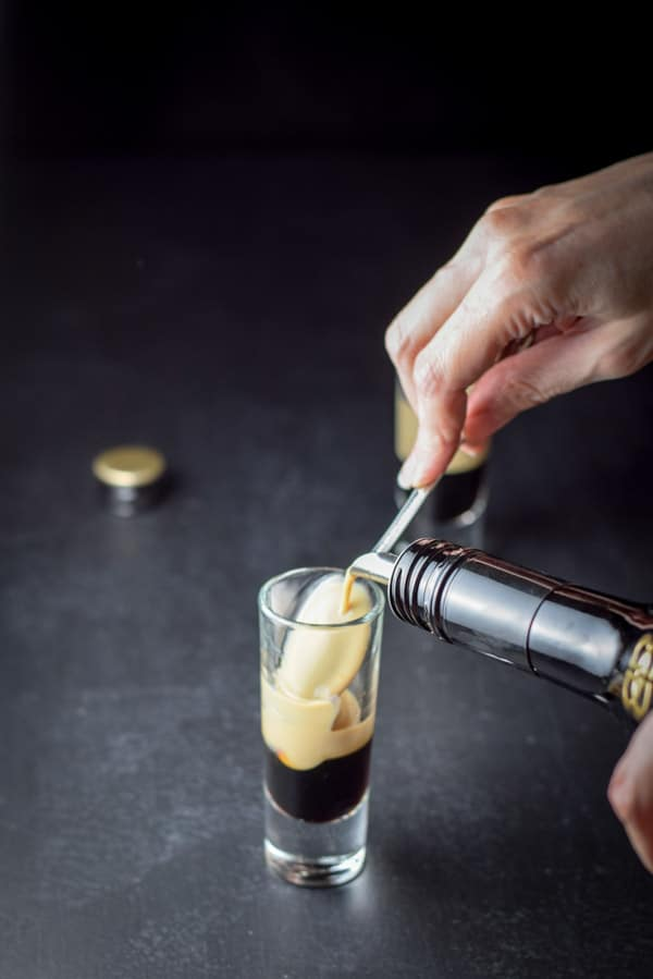 A female hand pouring Bailys Irish Cream over the back of a spoon into a shot glass that has kahlua in it already