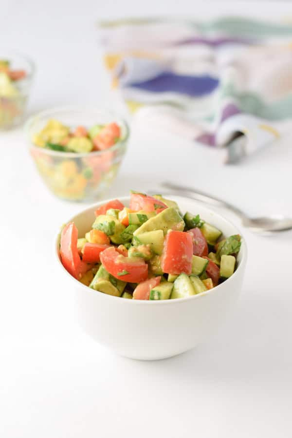 A small bowl filled with avocado tomato salad with a few more bowls and a napkin in the background
