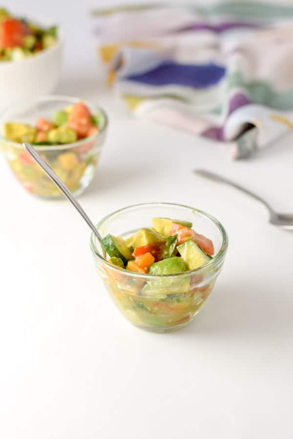 A few clear bowls with the avocado mixture in it and a very colorful napkin in the background