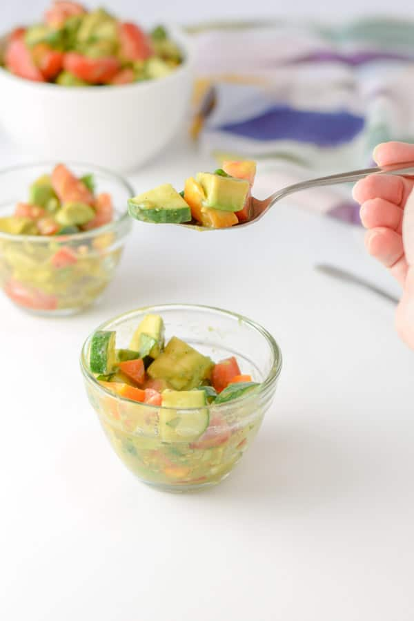 A forkful of of avocados, cucumber and tomatoes held over a bowl with more of the salad in it