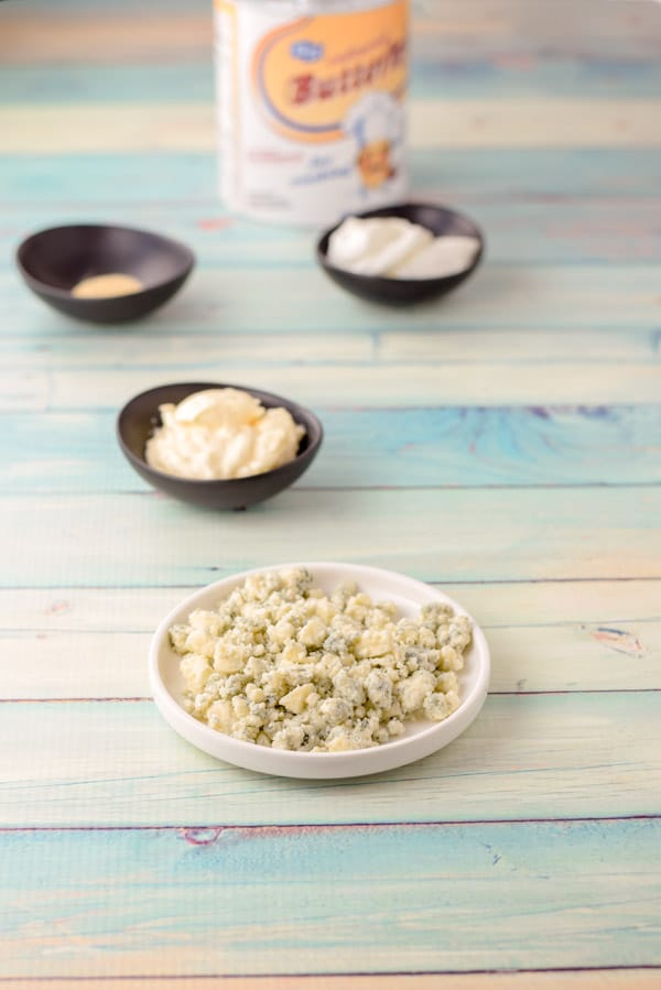 Blue cheese, sour cream, mayonnaise, spices and buttermilk on a green background