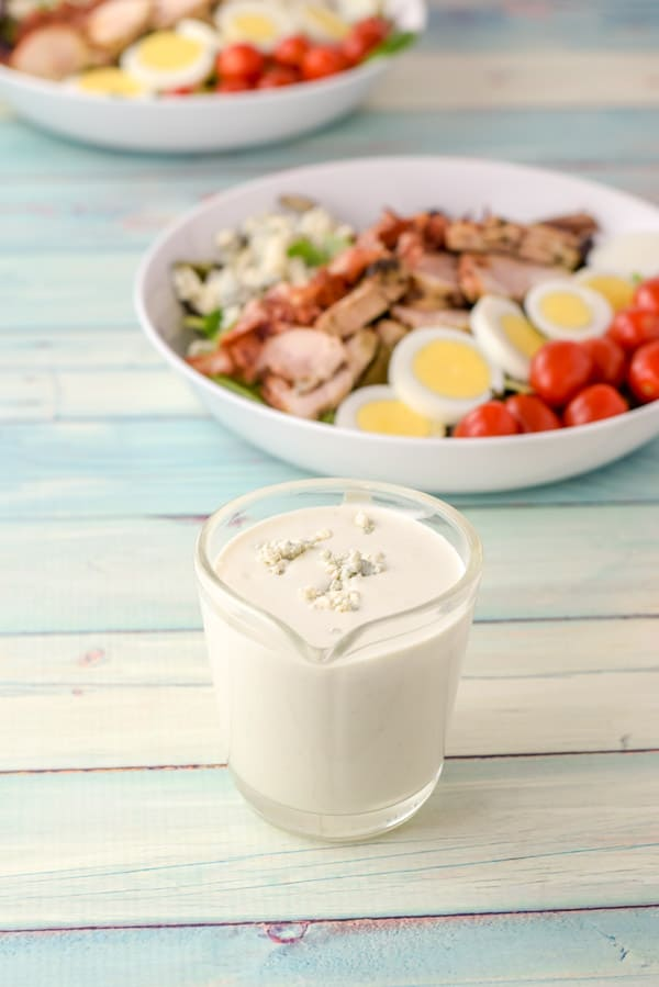 Dressing with blue cheese crumbled on top in a clear glass pitcher with two salads in the background