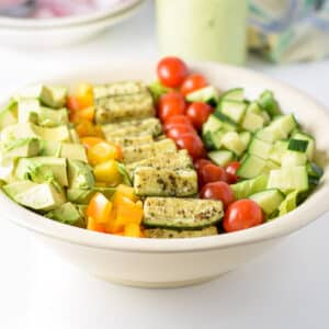 A bowl with lots of vegetables on the salad - square