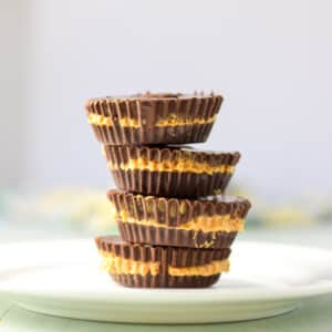 Vertical view of a stack of peanut butter cups on a white plate - square
