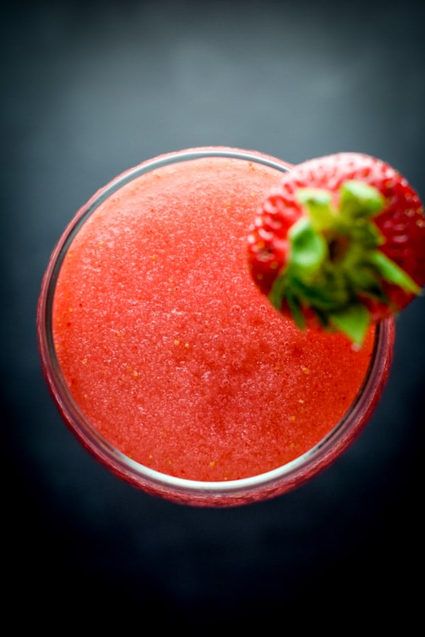 Overhead view of the frozen cocktail and a strawberry out of focus