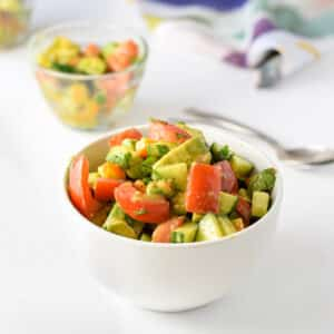 A white bowl filled with avocados, tomatoes and more vegetables, with a few smaller bowls in the background