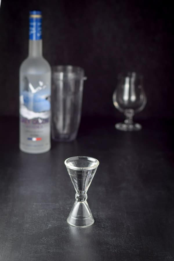 Vodka measured out with the bottle, blender container and glass in the background