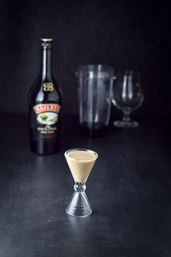 Irish cream measured out with the bottle, container and tulip glass in the background
