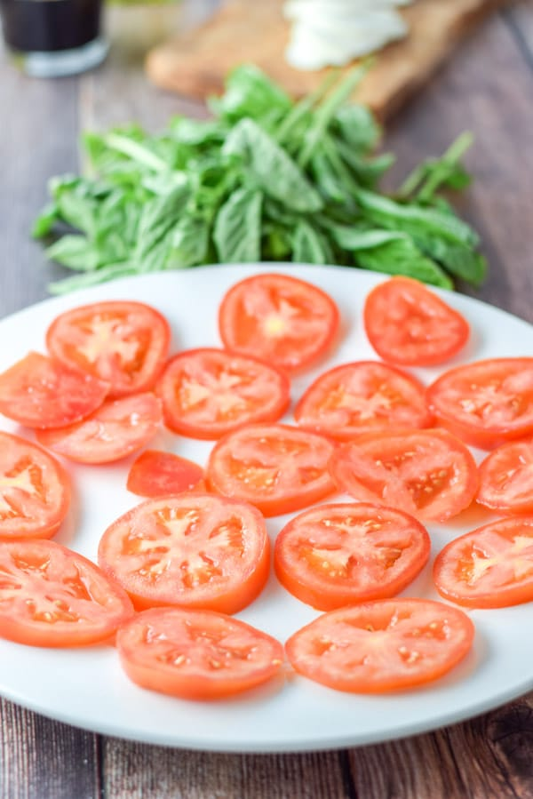 A white plate with tomato slices with basil, sliced cheese and vinegar in the background