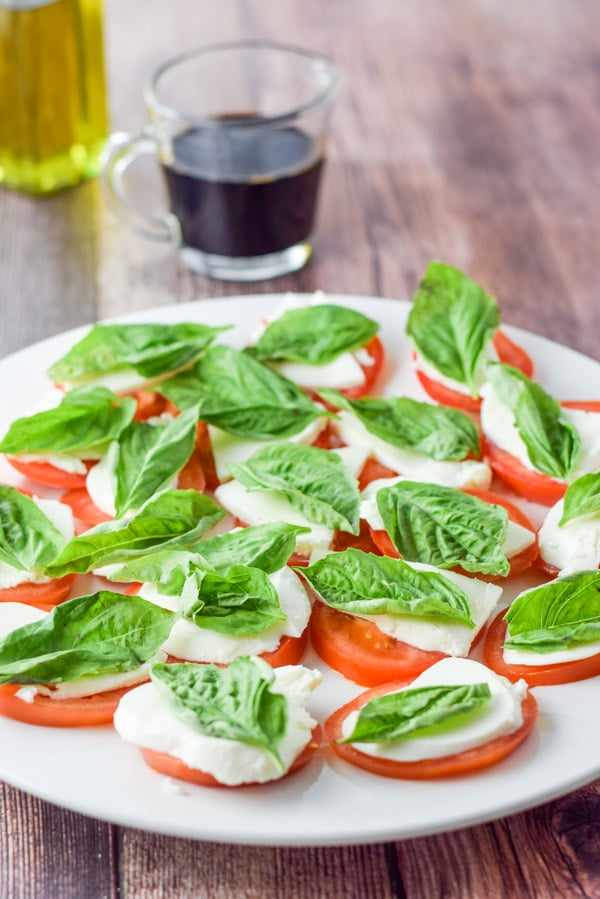 Basil on the cheese and tomato slices with oil and vinegar in the background