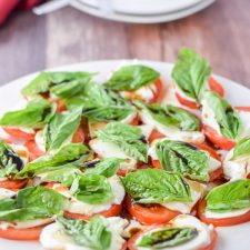 White plate with the tomato, basil and cheese salad with two other places in the background