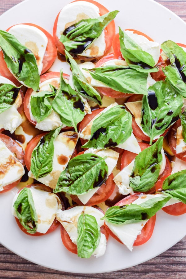 Overhead view of a round white plate with tomato slices with cheese, basil and balsamic vinegar