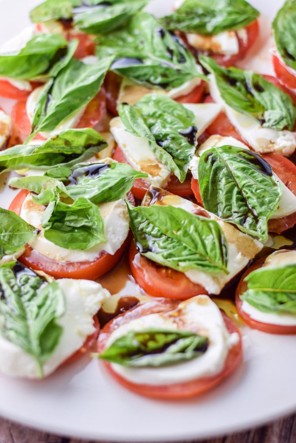 A white plate with tomatoes topped with cheese, basil and balsamic vinegar