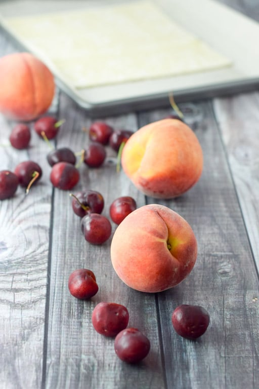 cherries and peaches in front of a pan lined with parchment paper and puff pastry on it