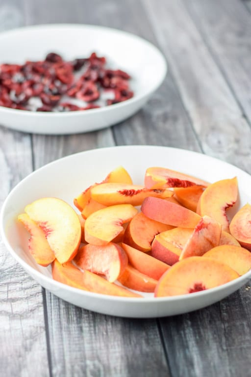 Two white deep bowls with sliced peaches in one and cherries in the other