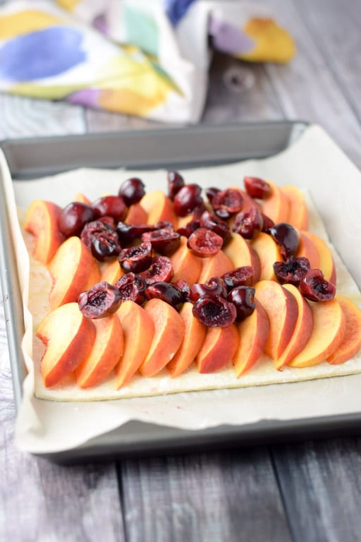 Peaches lined up on puff pastry with cherries sprinkled on top