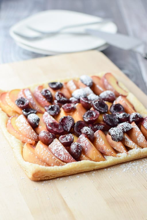 A wooden board with a fruit tart with two plates in the background