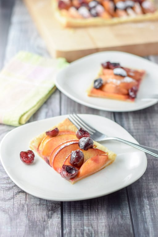 Two square plates with the fruit tart on them with a board with the rest of the tart in the background
