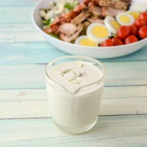 Dressing with blue cheese crumbled on top in a clear glass pitcher with two salads in the background - square