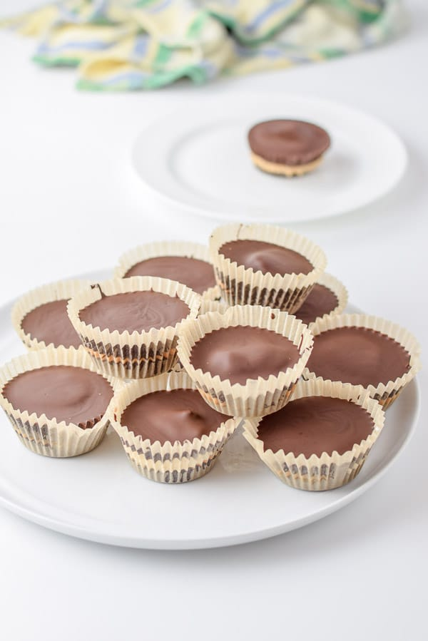 A big pile of dark chocolate cups on a plate and a lone one on a smaller plate in the background
