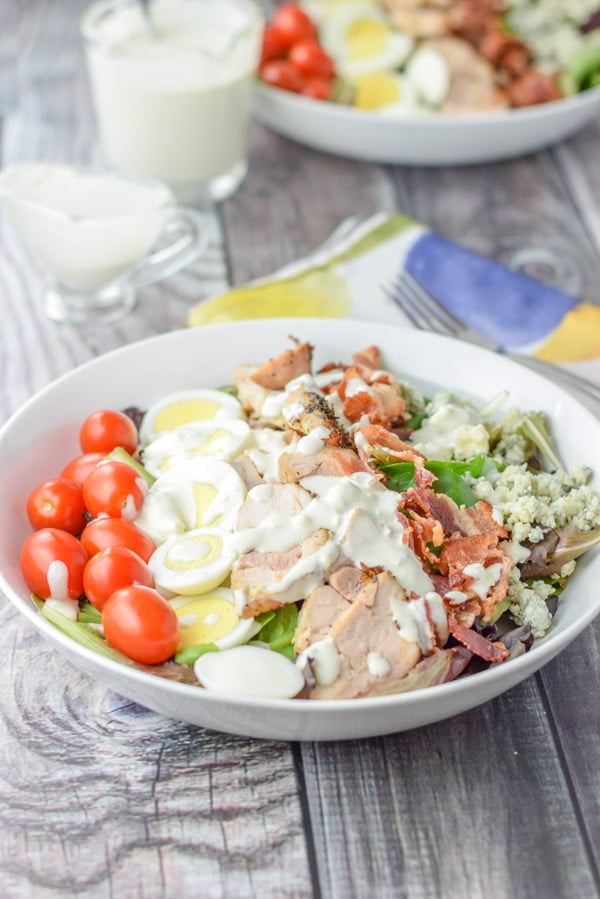 Blue cheese dressing fully poured onto the colorful lined salad with another bowl in the background as well as the dressing in containers