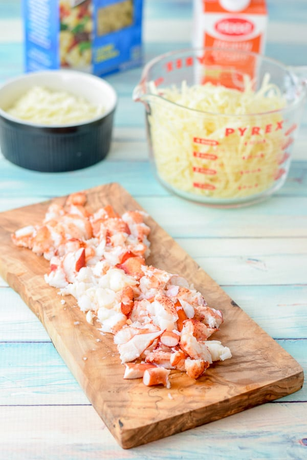 Lobster cut up on a board, with cheese, cream and elbow macaroni behind it
