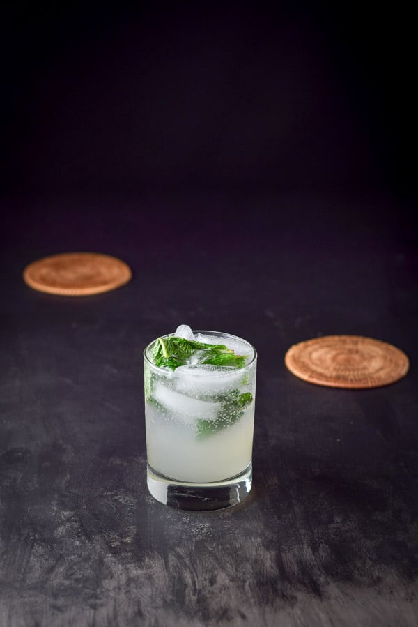 Mint floating on the ginger mojito with coasters in the background
