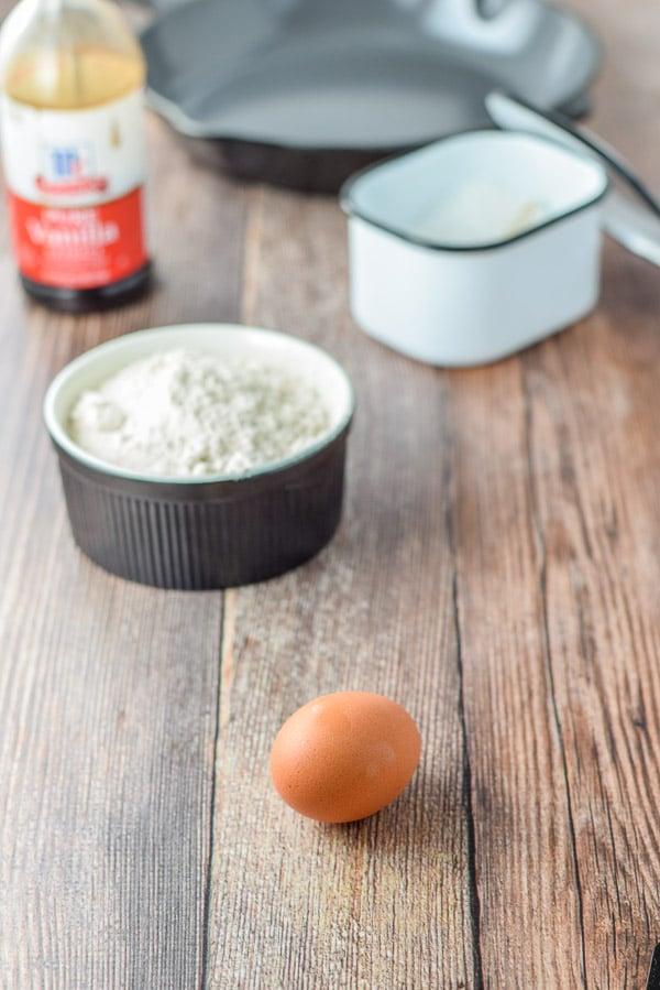 An egg, flour, salt and vanilla on the wooden table