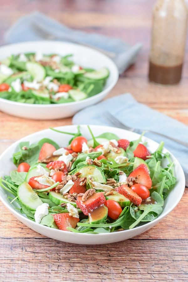 The strawberry arugula salad with balsamic dressing on it