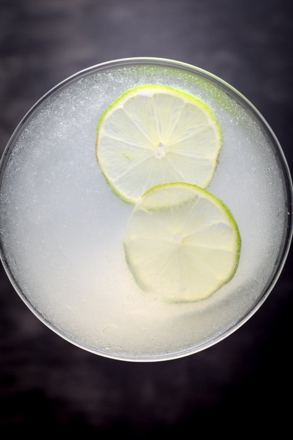 Overhead view of the gimlet with two thin lime wheels floating in it