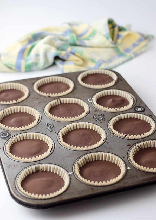 The muffin pan with the dark chocolate cups out of the freezer
