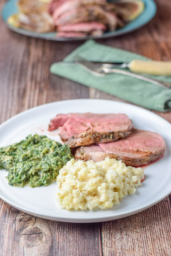 Mashed root, creamed spinach and slices of lamb on a white plate. There is a big plate with slices of lamb in the background