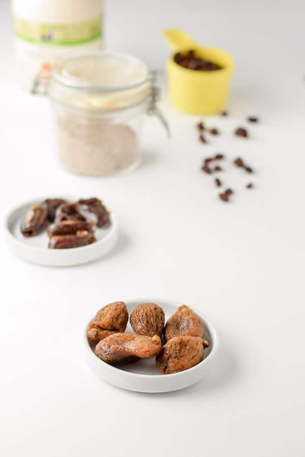 Figs, dates, chia seeds, oats and raisins on a white background