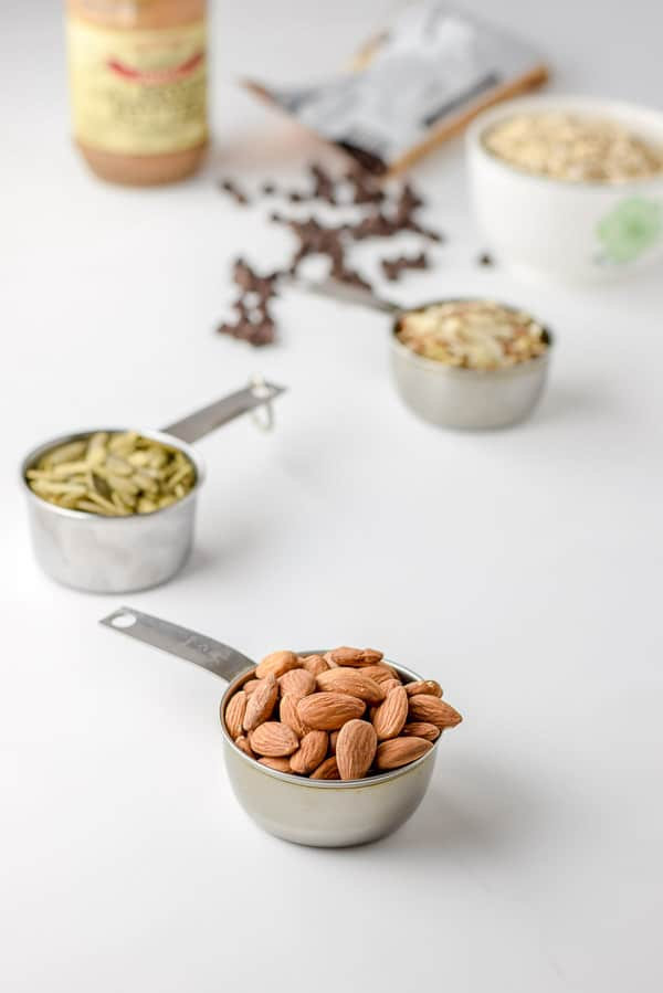 Almonds, pumpkin seeds, slivered almonds, rolled oats, chocolate chips and almond butter on a white background