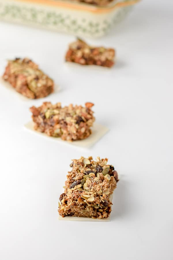 Rectangles cut up into granola bars. There are four of them on the table with the baking pan in the background