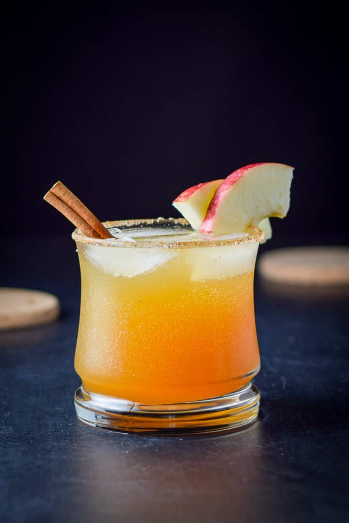 Vertical view of the spritzer with a cinnamon stick and apple slices on the rim