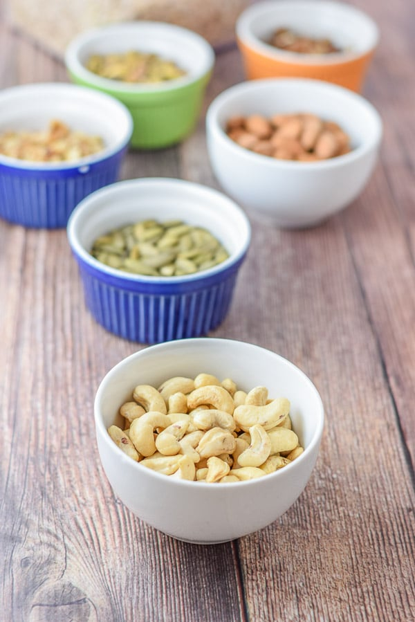 Bowls of cashews, almonds, pistachios, pecans, walnuts and pumpkin seeds