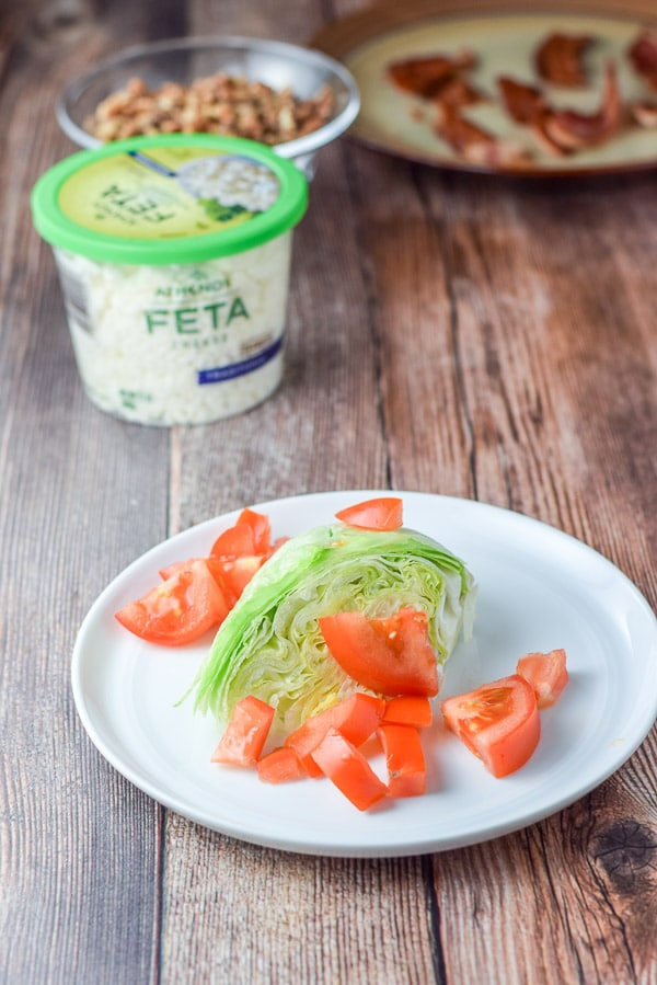 Tomato chunks added to the lettuce on a white plate with other ingredients in the background