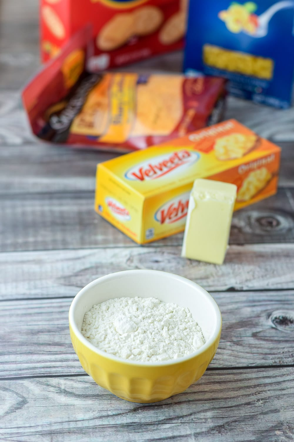 Flour, butter, Velveeta, cheddar cheese, elbow macaroni and Ritz crackers on a grey wooden table
