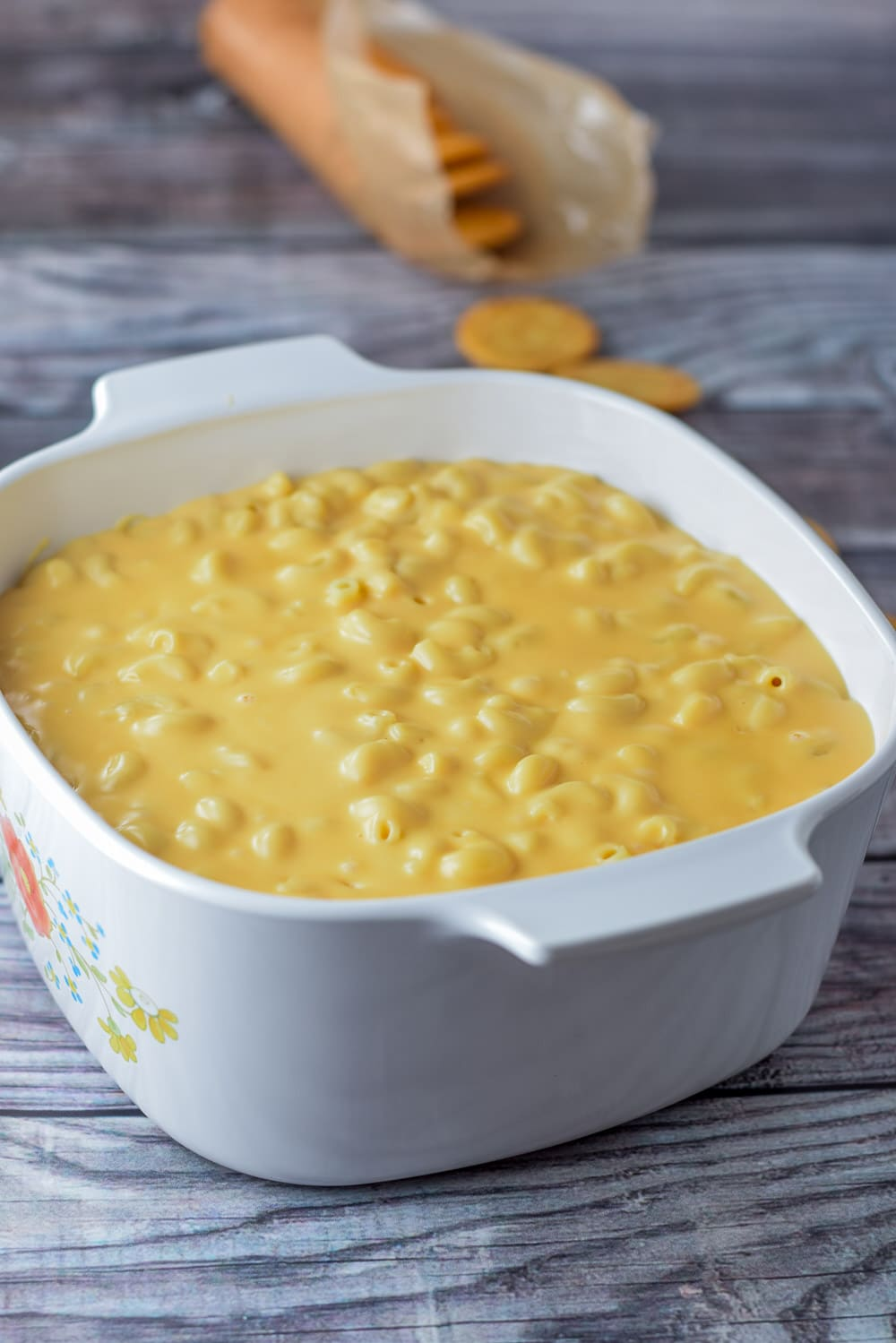Elbow macaroni and cheese sauce in a casserole dish with some Ritz crackers in the background