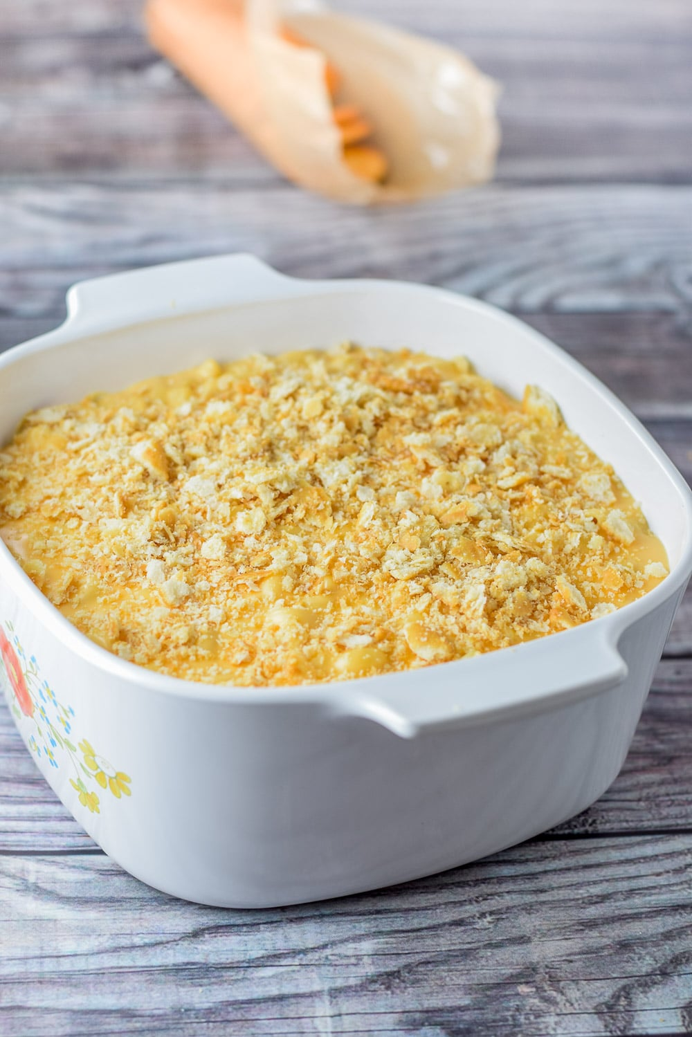 Ritz crackers crumbled on cheese sauce and macaroni in the baking dish