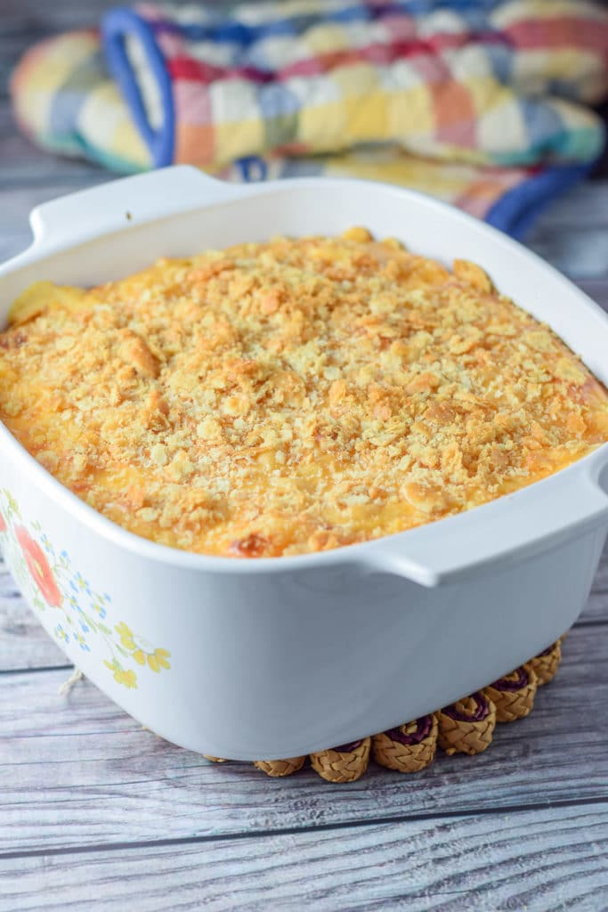 The mac and cheese fresh out of the oven with two oven mitts in the background