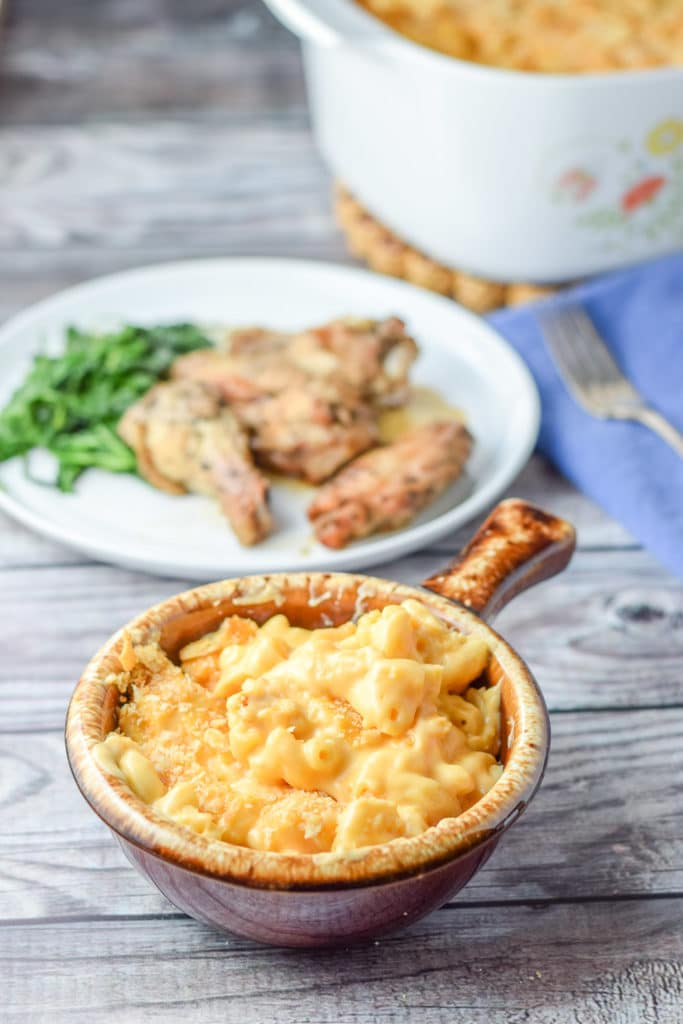 A crock filled with the mac and cheese with the casserole dish and a plate of chicken wings and spinach behind it