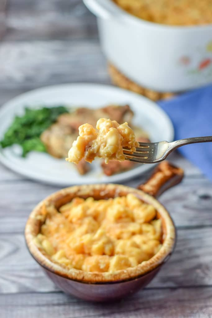 A forkful of mac and cheese over the crock with the casserole dish and wings behind it