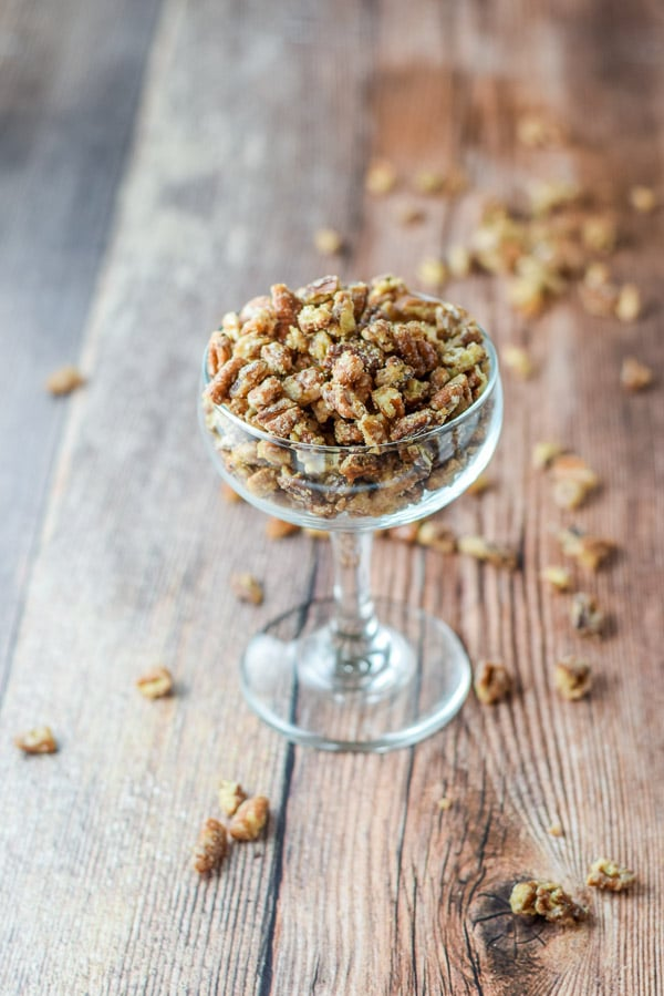A coupe glass with the candied pecans in them and more pecans strewn across the wooden table