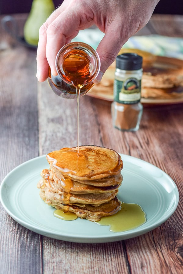 A hand holding a small glass bottle of maple syrup and being poured onto some pancakes. There is cinnamon and more pancakes in the background