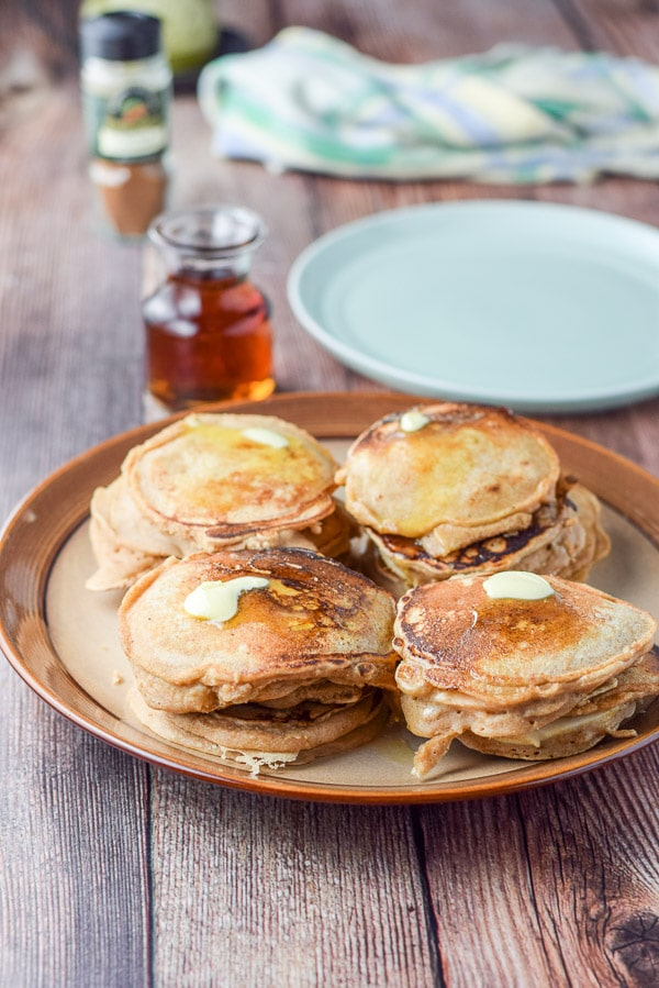 A brown plate with 4 stacks of pancakes and butter on them. There is a green plate, maple syrup and spices in the background